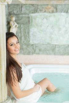 Jovem relaxante na banheira de hidromassagem