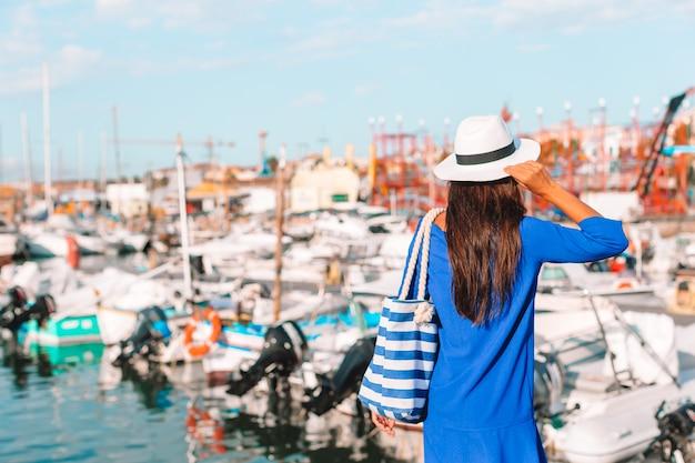 Jovem relaxante na doca perto dos barcos em dia ensolarado
