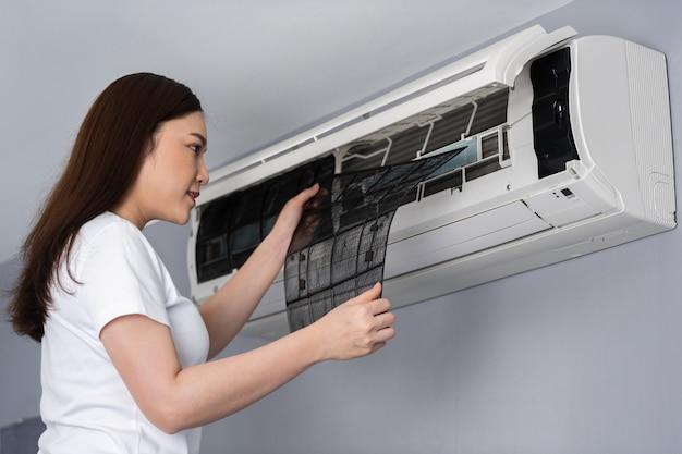 Jovem removendo o filtro de ar do ar condicionado para limpar em casa