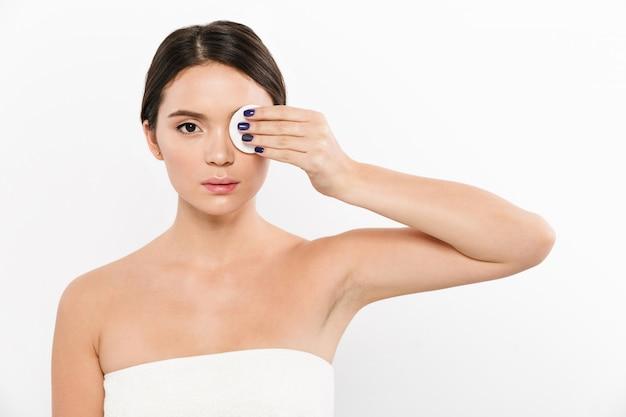 Jovem remover maquiagem com esponja de algodão isolada