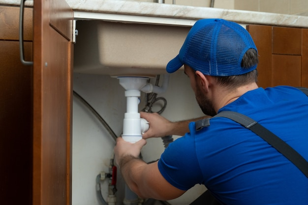 Jovem reparador com ferramentas nas mãos e um boné azul está consertando a pia da cozinha