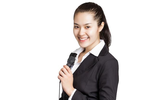 Jovem repórter de notícias asiáticas segurando um microfone com uma carinha sorridente isolada no branco.