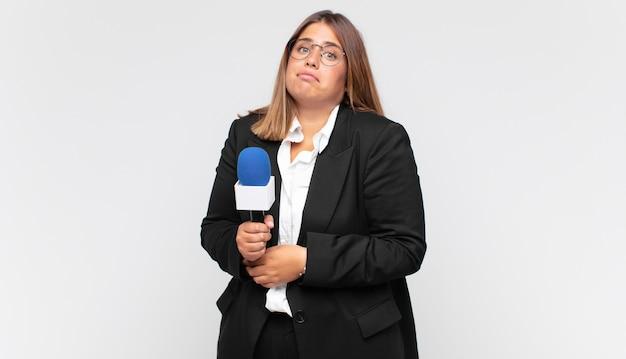 Jovem repórter encolhendo os ombros, sentindo-se confusa e incerta, duvidando com os braços cruzados e olhar perplexo