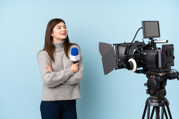 Jovem repórter mulher segurando um microfone e reportando notícias olhando para o lado