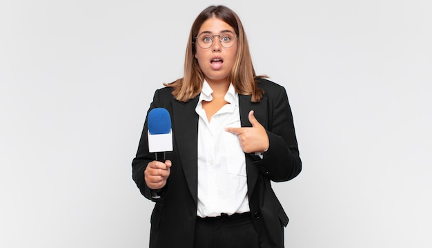 Jovem repórter parecendo chocada e surpresa com a boca bem aberta, apontando para si mesma