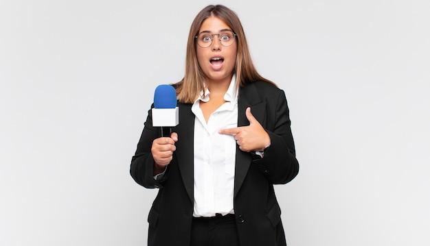 Jovem repórter se sentindo feliz, surpresa e orgulhosa, apontando para si mesma com um olhar empolgado e surpreso