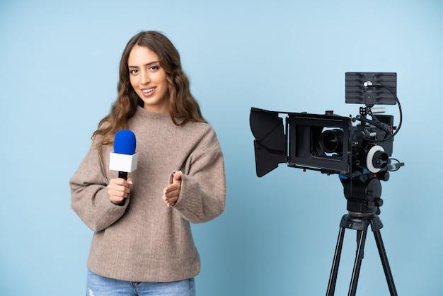 Jovem repórter segurando um microfone e relatando notícias aperto de mão depois de um bom acordo