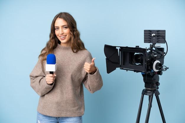 Jovem repórter segurando um microfone e reportar notícias dando um polegar para cima gesto