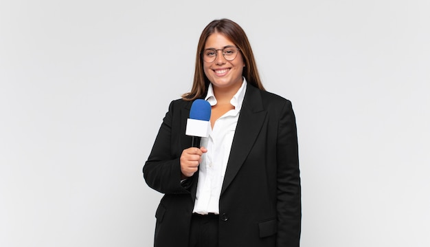 Jovem repórter sorrindo feliz com a mão no quadril e com uma atitude confiante, positiva, orgulhosa e amigável