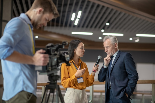 Jovem repórter tendo entrevista com empresário famoso