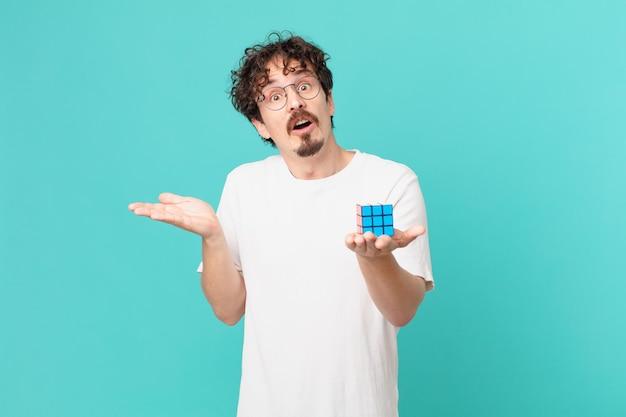 Jovem resolvendo um problema de inteligência parecendo surpreso e chocado, com o queixo caído segurando um objeto