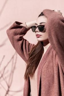 Jovem retrato bonito em óculos de sol da moda com casaco ao ar livre perto da parede rosa em dia ensolarado. linda garota com a pele limpa com lábios sensuais endireita o cabelo luxuoso em pé perto de um prédio vintage.