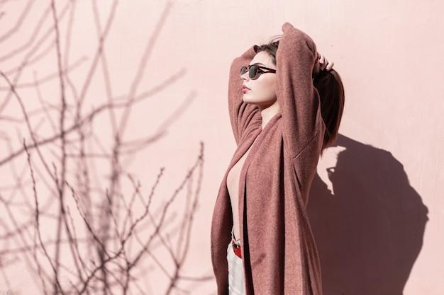 Jovem retrato bonito em óculos de sol da moda com casaco perto da parede rosa na cidade em dia ensolarado. garota sexy com pele limpa com lábios sensuais endireita o cabelo luxuoso em pé perto de um prédio vintage.