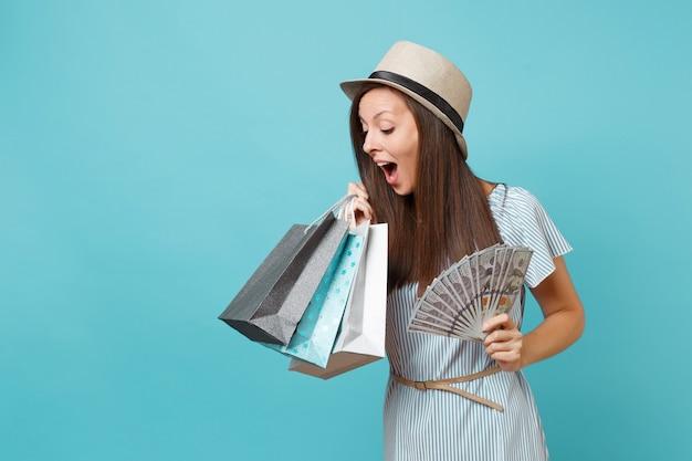 Jovem retrato com vestido de verão, chapéu de palha segurando pacotes sacos com compras depois de fazer compras, muitas notas de dólares, dinheiro vivo, isolado sobre fundo azul. copie o espaço para anúncio.