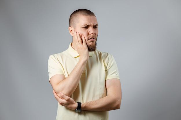 Jovem retrato de camiseta amarela, segurando sua bochecha, olhando para o lado em cinza.