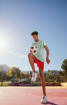 Jovem retrato jogando futebol