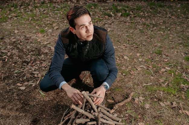 Jovem retrato preparando uma pilha de madeira para acender o fogo. camping, conceito de estilo de vida natural.