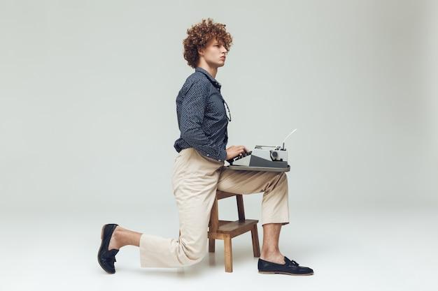 Jovem retrô sério segurando a máquina de escrever.