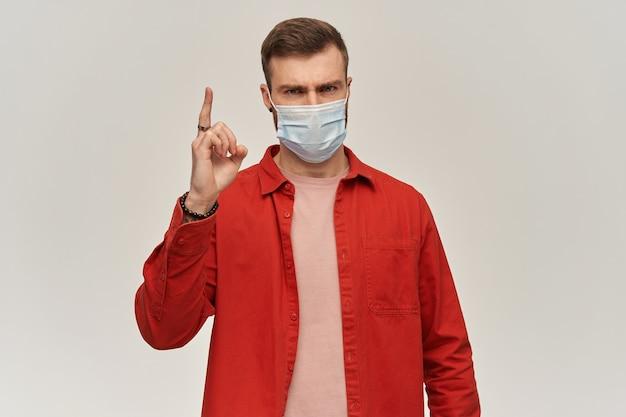 Jovem rigoroso com barba em camisa vermelha e máscara higiênica para prevenir infecção, alerta e apontando para cima com o dedo sobre a parede branca