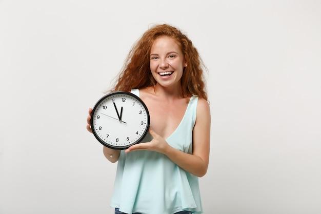 Jovem rindo garota ruiva bonita alegre em roupas leves casuais posando isolado no fundo da parede branca, retrato de estúdio. conceito de estilo de vida de pessoas. simule o espaço da cópia. segurando relógio redondo.