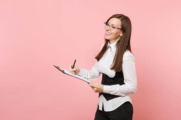 Jovem rindo linda mulher de negócios em copos, escrevendo sobre o tablet da área de transferência com documentos de papéis isolado no fundo rosa. senhora chefe. riqueza de carreira de realização. copie o espaço para anúncio.