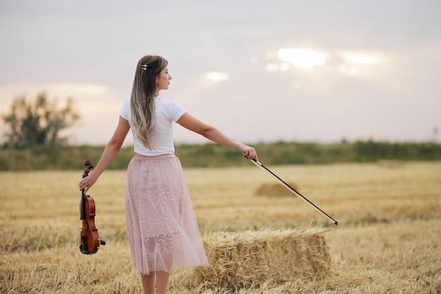 Jovem romântica com cabelos soltos, segurando um violino em um campo após a colheita