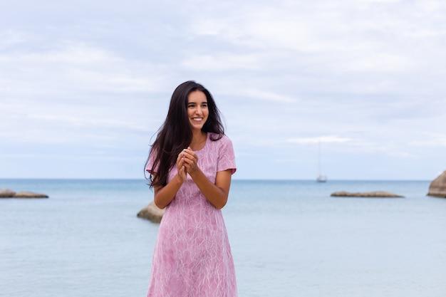 Jovem romântica com longos cabelos escuros em um vestido na praia sorrindo e rindo se divertindo sozinha