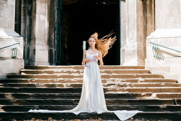 Jovem romântica e elegante com cabelo esvoaçante em um longo vestido branco, posando nas escadas do antigo palácio