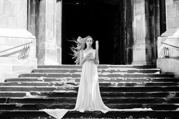 Jovem romântica e elegante com cabelo esvoaçante em um vestido longo branco posando nas escadas do antigo palácio