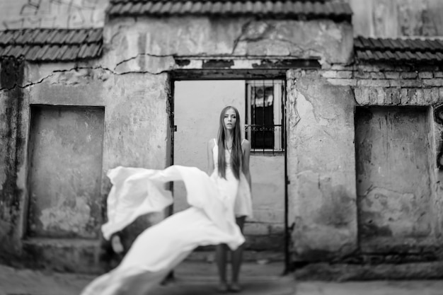 Jovem romântica e elegante com um vestido branco esvoaçante posando sobre edifícios antigos de pedra