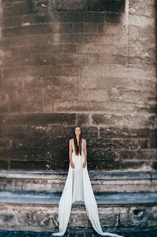 Jovem romântica e elegante em um vestido longo branco esvoaçante posando sobre uma parede de pedra antiga Foto Premium