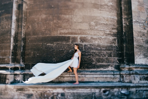 Jovem romântica e elegante em um vestido longo branco esvoaçante posando sobre uma parede de pedra antiga
