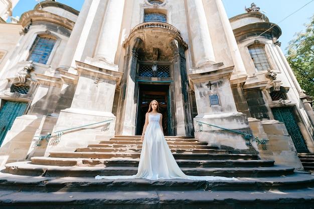 Jovem romântica e elegante em um vestido longo branco posando nas escadas do antigo palácio