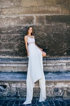 Jovem romântica e elegante em um vestido longo branco posando sobre um muro de pedra.