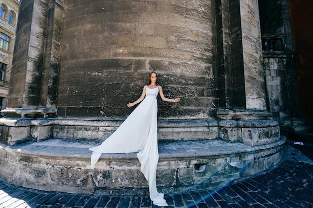 Jovem romântica e elegante em um vestido longo branco posando sobre um muro de pedra. Foto Premium