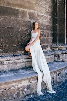 Jovem romântica e elegante em um vestido longo branco posando sobre uma parede de pedra antiga