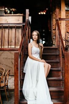 Jovem romântica e pensativa em um vestido longo branco sentada na escada