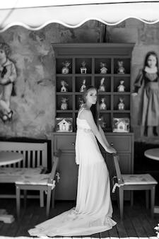 Jovem romântica elegante em um vestido branco posando sobre uma parede decorada