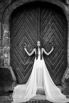 Jovem romântica elegante em um vestido longo branco posando sobre uma porta antiga
