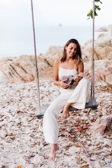 Jovem romântica feliz e calma mulher caucasiana com ukulele na praia tropical rochosa ao pôr do sol
