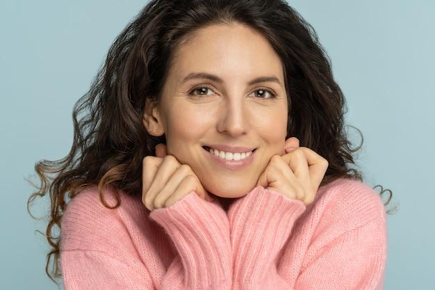 Jovem romântica mantém as mãos embaixo do queixo, olhando para a câmera, sorrindo, tem dentes brancos, usa um suéter rosado