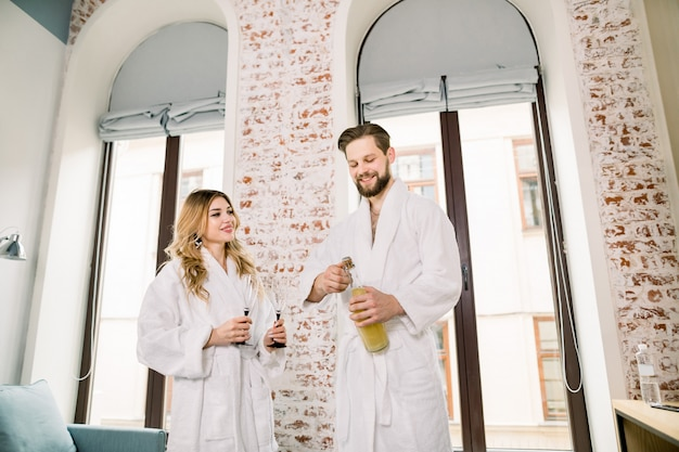 Jovem romântico em roupão branco, abrindo uma garrafa de champanhe enquanto relaxa com seu parceiro no quarto de hotel moderno