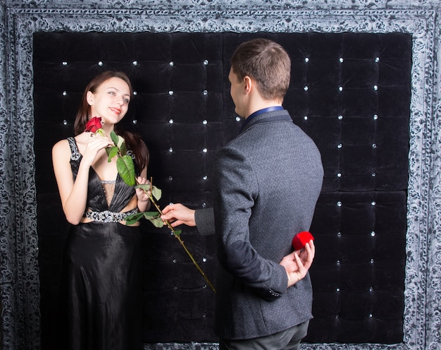 Jovem romântico pedindo a uma linda jovem em um elegante vestido de coquetel preto em casamento, presenteando-a com uma rosa antes de produzir o anel