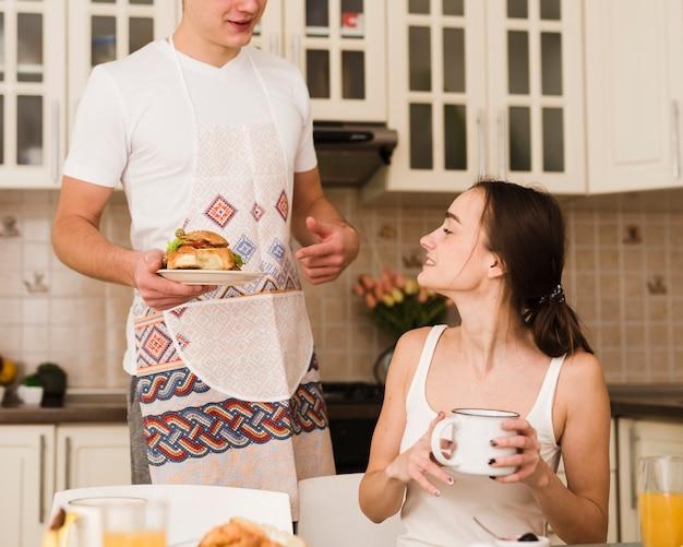 Jovem romântico servindo café da manhã com mulher