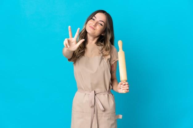Jovem romena segurando um rolo de massa no azul feliz e contando três com os dedos