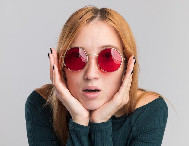 Jovem ruiva animada e ruiva com sardas em óculos de sol coloca as mãos no queixo isolado na parede branca com espaço de cópia