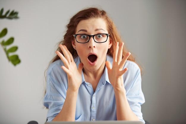 Jovem ruiva atônita, funcionária de escritório, de óculos e camisa azul