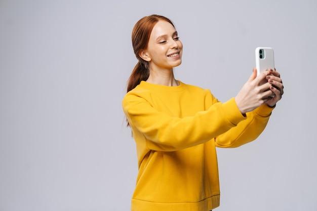 Jovem ruiva bonita assistindo a uma videochamada com o amante segurando um telefone inteligente na mão, tirando uma selfie