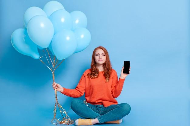 Jovem ruiva calma segurando um telefone celular com a tela em branco e vazia