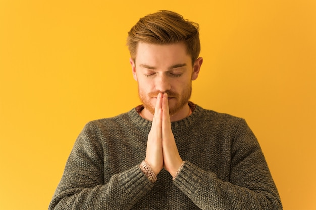 Jovem ruiva cara closeup rezando muito feliz e confiante